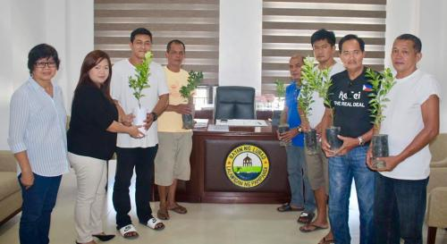 Lubao Mayor Esmie Pineda (2nd from Left), assisted by Municipal Agriculture Officer Maria David (left), hands over calamansi seedlings to beneficiaries from Sto. Domingo Free Farmers Association